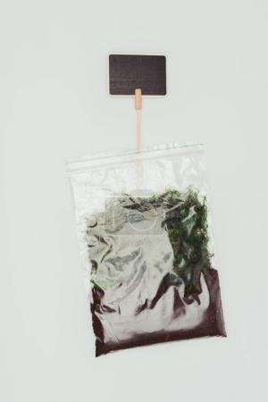 top view of ziplock plastic bag with dried plants, soil and blackboard isolated on white, earth day concept