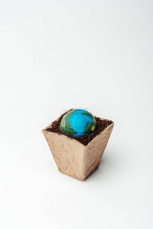 earth model in flower pot with soil isolated on white, earth day concept