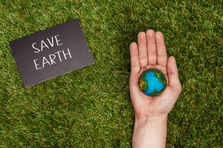 cropped image of man holding earth model in hand with sign save earth on green grass, earth day concept