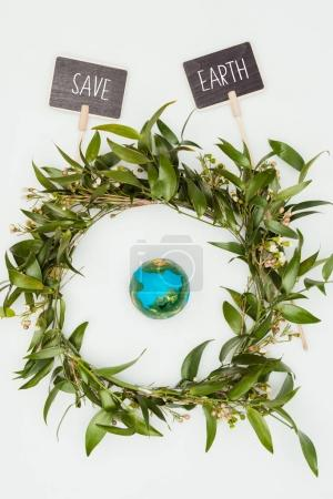 top view of earth model inside wreath with signs save earth isolated on white, earth day concept