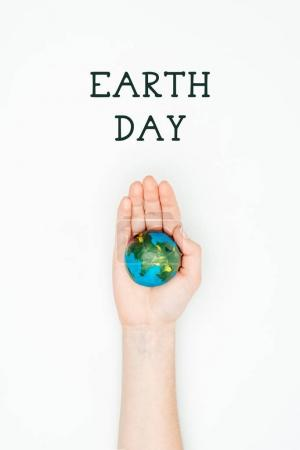 cropped image of woman holding earth model on hand under sign earth day isolated on white
