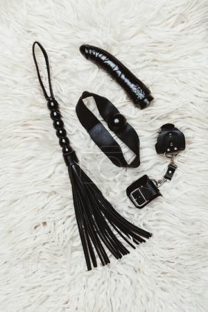 Black bdsm gag and vibrator with whip on white carpet