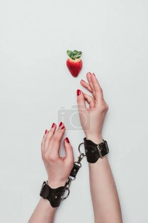 Female hands tied with leather handcuffs reaching for strawberry isolated on white