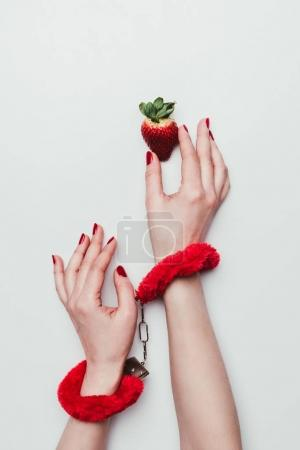 Female hands in red fluffy handcuffs reaching for strawberry isolated on white