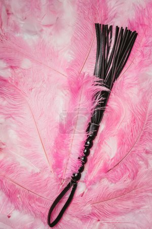 Black strict leather flogging whip on pink feathers