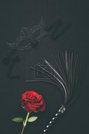 Lacy mask and black whip with rose flower isolated on black