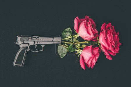 Photo for Bouquet of red roses shooting from gun isolated on black - Royalty Free Image