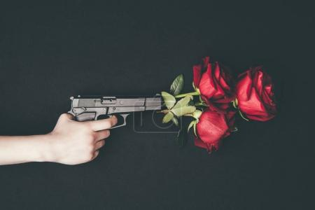 Woman shooting gun with red roses isolated on blac...