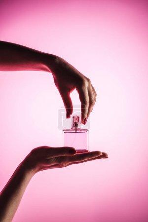 Photo pour Vue recadrée de la femme tenant le flacon de parfum pulvérisateur, isolé sur rose - image libre de droit