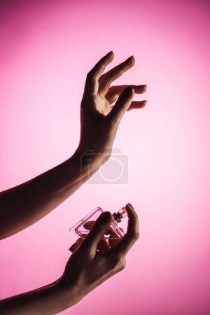 Photo pour Vue recadrée de femme sensuelle pulvérisation parfum de part, isolé sur rose - image libre de droit