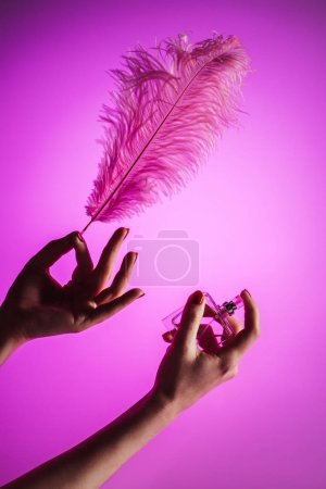 cropped view of sensual woman spraying perfume on feather, isolated on pink