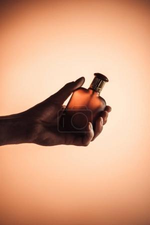 Photo pour Vue recadrée de main mâle avec parfum, isolé sur orange - image libre de droit