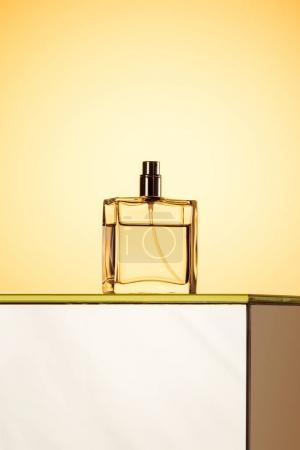 stylish spray bottle with perfume, on yellow