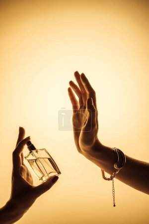 cropped view of woman spraying perfume on hand to feel fragrance, isolated on yellow