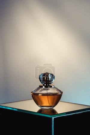 spray bottle with perfume on glass table