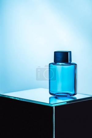 mens perfume in blue spray bottle, on blue