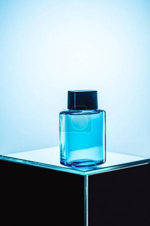 mens fragrance in blue spray bottle, on blue