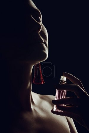 silhouette of girl spraying perfume on her neck, isolated on black
