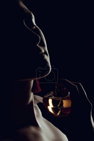 silhouette of sensual woman spraying perfume on neck, isolated on black