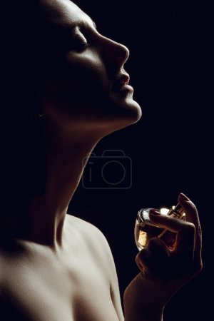Photo for Silhouette of sensual girl spraying perfume on neck, isolated on black - Royalty Free Image