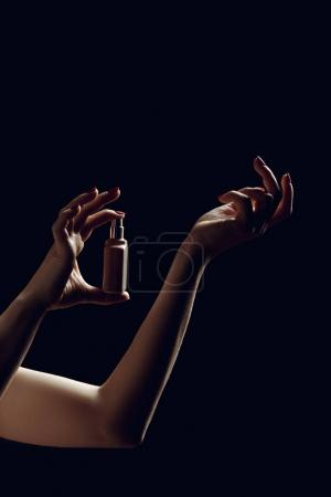 silhouette of female hands spraying perfume, isolated on black