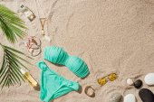 top view of blue bikini with various accessories and pebbles on sandy beach