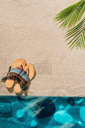 top view of stylish flip flops on sandy beach