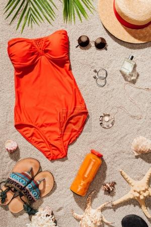 top view of stylish red swimsuit with various accessories on sandy beach