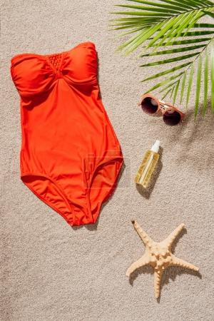 top view of stylish red swimsuit with body lotion and sunglasses on sandy beach