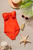 top view of stylish red swimsuit with body lotion and accessories on sandy beach
