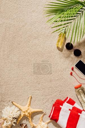 Photo for Top view of striped towel with various objects lying on sandy beach - Royalty Free Image