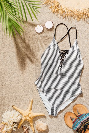 top view of stylish swimsuit with sunglasses and flip flops lying on sandy beach