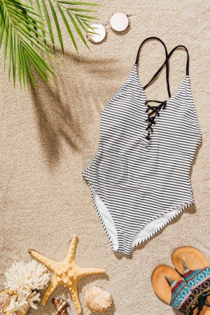 Photo for Top view of swimsuit with sunglasses and flip flops lying on sandy beach - Royalty Free Image