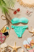 top view of beautiful bikini and various accessories lying on sandy beach
