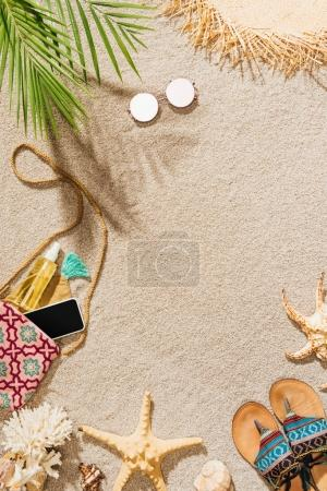 top view of stylish female accessories lying on sandy beach