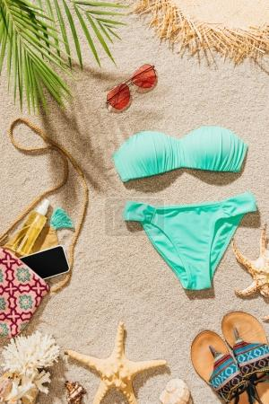 top view of stylish bikini and various accessories lying on sandy beach