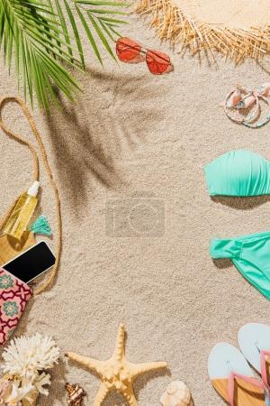 Photo for Top view of bikini and various accessories lying on sandy beach - Royalty Free Image