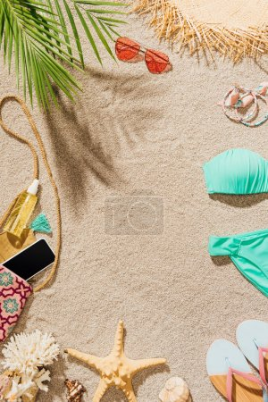 top view of bikini and various accessories lying on sandy beach