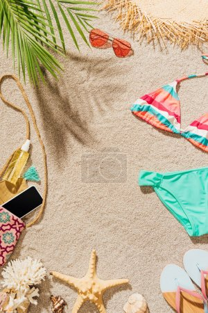 top view of bikini and accessories lying on sandy beach