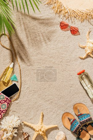 top view of different female accessories lying on sandy beach