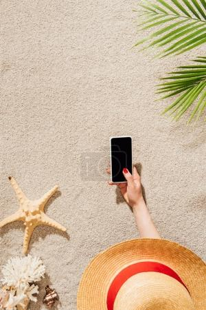 cropped shot of woman in hat using smartphone while lying on sandy beach