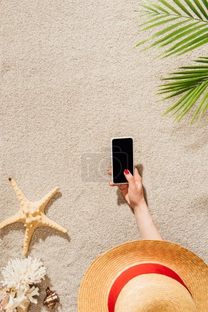 Photo for Cropped shot of woman in hat using smartphone while lying on sandy beach - Royalty Free Image