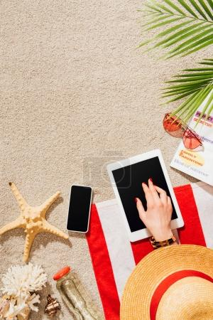 cropped shot of woman in hat using gadgets while relaxing on sandy beach