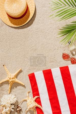 top view of striped towel with straw hat and sunglasses on sandy beach
