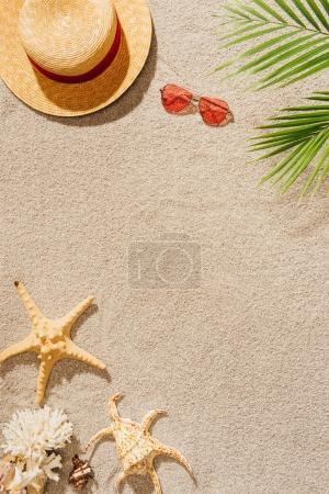 top view of straw hat with sunglasses on sandy beach