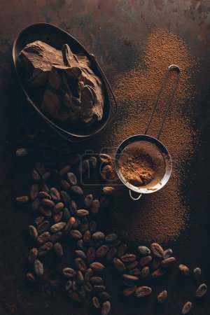 Photo for Delicious chocolate pieces, cocoa beans, powder and sieve on dark surface - Royalty Free Image