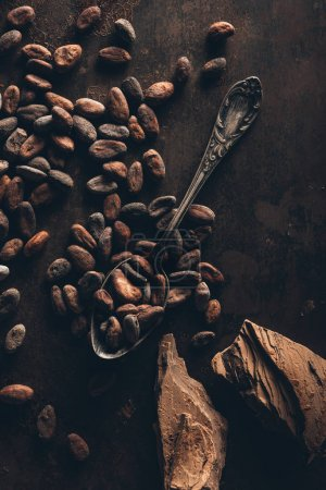top view of cocoa beans, vintage spoon and chocolate pieces on dark surface