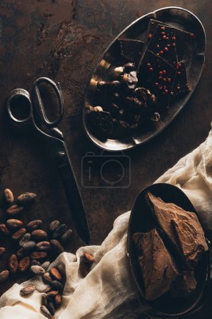 top view of vintage scissors, cocoa beans, cloth, chocolate pieces and nuts on dark surface