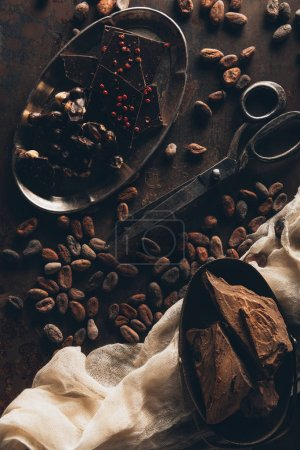 vintage scissors, cocoa beans, cloth, chocolate pieces and nuts on dark surface