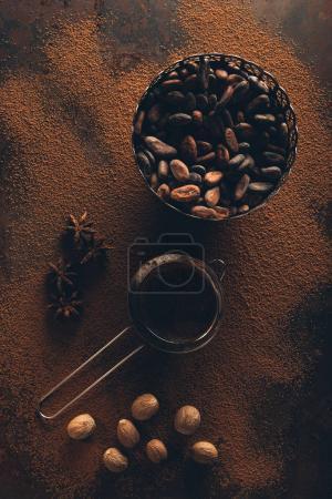 Foto de Vista superior de granos de cacao gourmet en tazón vintage, tamiz y anís estrellado en polvo de cacao - Imagen libre de derechos